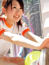 Naoko Sawano in sports outfit plays with balls in garden